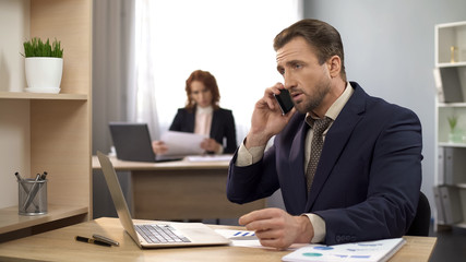 Male typing on laptop at office desk, answering mobile phone, customer care