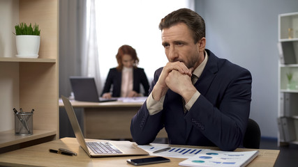 Man finishing typing on laptop, sitting content at desk, exceeded expectations