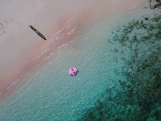 Aerial view of a woman on a pink inflatable flamingo float, Pink Beach, East Nusa Tenggara, Indonesia