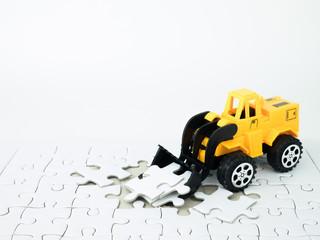 Toy bulldozer with Jigsaw puzzle on white background