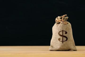 Asack of money over wooden desk