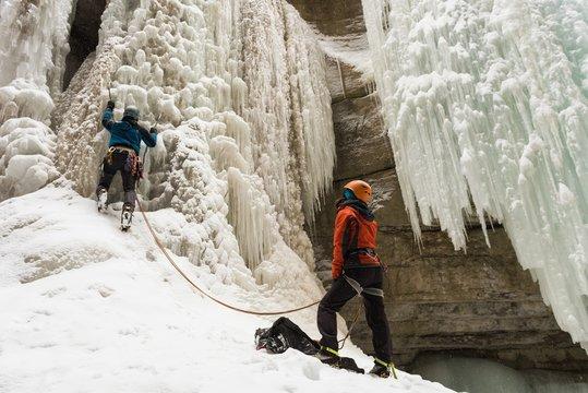 Rock climbers climbing rocky mountain during winter