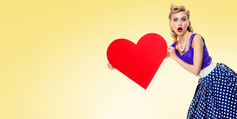 Smiling woman holding heart symbol, dressed in pinup style
