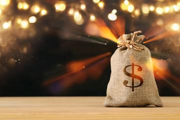 A sack of money over wooden desk and glitter black background.