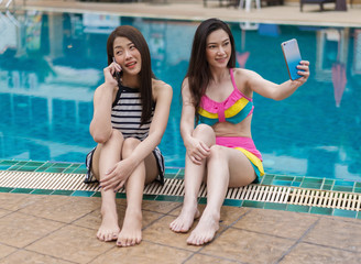 two young women friends using mobile phone in swimming pool