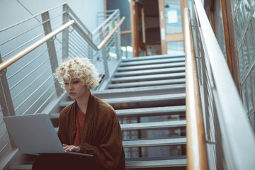 Woman using laptop on staircase in library