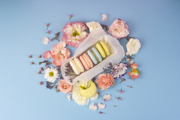 Multicolored macaroons cakes with big and small different flower buds in a gift box with wrapping paper on a blue background.