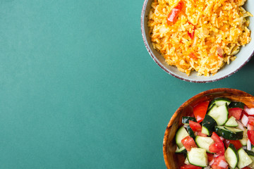 Traditional National Mexican Tomato Rice Stewed Pilaf with Hot Chili Peppers Garlic in Turquoise Bowl. Fresh Cucumber Onion Salsa Salad in Wooden Dish. Green Background. Top View Flat Lay. Copy Space