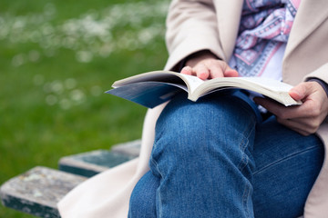 girl at the park reading a book