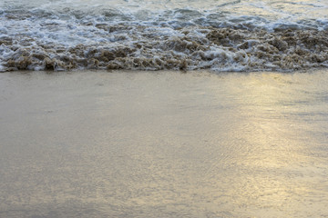Sea waves hit the beach shore.