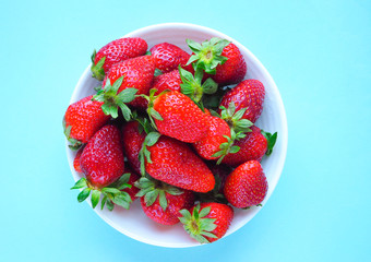 Fresh strawberry in white plate on blue background. The view from the top.
