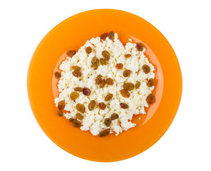 Grainy cottage cheese with raisin in orange plate on white