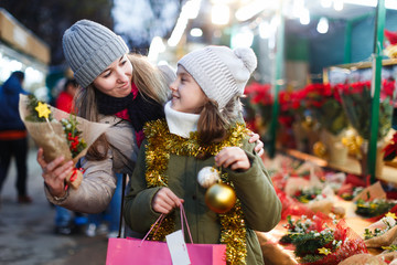 Woman and her daughter are preparing for Christmas and choosing gifts for their family