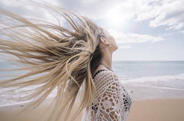 A girl on the beach loosing hair.