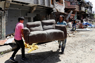Residents retrieve a sofa after they were allowed to return to their homes for the first time since the battle between government troops and Islamic State militants began on May 2017, at the Islamic city of Marawi