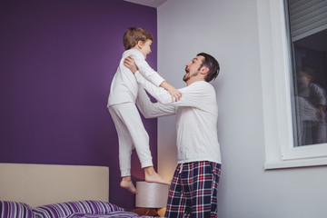 Happy father and son playing in bedroom and having fun in the evening.