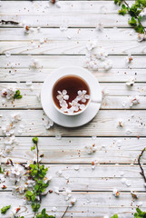 Cup of tea and spring apricot blossom on a wooden background. Rustic. Overhead view.