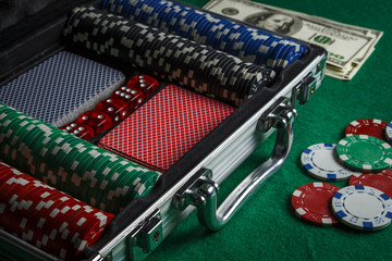 A suitcase with playing cards, poker chips and dice near a pile of dollars