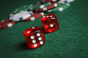 Dice on the poker table against the background of poker chips