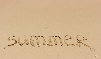 Hand inscription Summer on a wet sand in sunny day