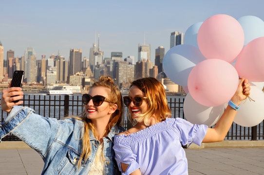 Beautiful women taking a selfie with her smartphone on New York view