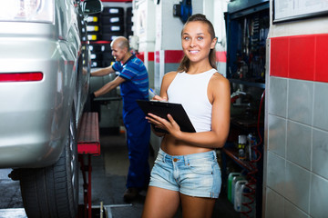 Girl with documents in auto workshop