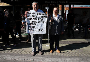 A demonstrator holds a placard as he takes part in a protest demanding an end to profiteering in the education system in Santiago