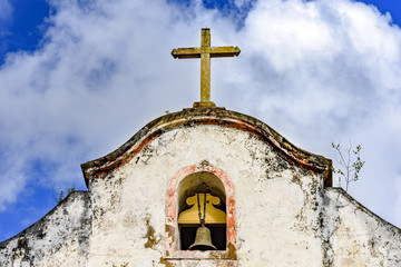 Bell and crucifix on top of old chapel in the historic city of Ouro Preto in Minas Gerais with blue sky and clouds in the background