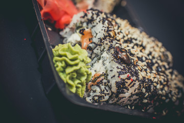 Ginger, green wasabi and sushi on a black plate