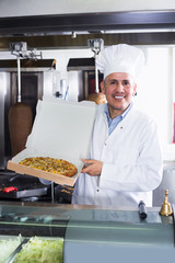 Cook serving fresh pizza to customer in restaurant