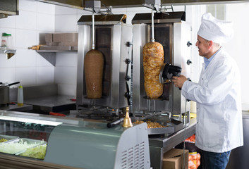 man chef wearing uniform cutting meat for kebab on kitchen in fast food restaurant
