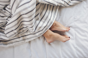 Female feet under blanket flat lay. Female beautiful feet with pedicure on the bed. Top view on the sleeping woman legs under the striped blanket