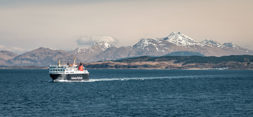 Ferry sailing between Oban and the Isle of Mull with snow capped highland peaks in the background