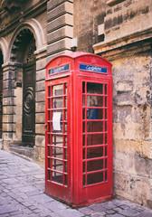 Red British vintage telephone booth in Valletta, Malta