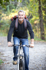 Gray-haired man smiling while riding bicycle in forest, Massachusetts, USA