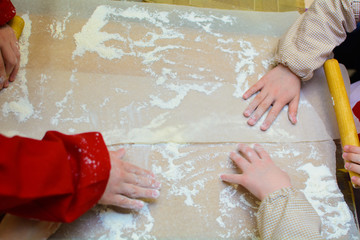 hands of children cooks spread the flour on the board