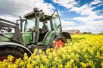 Landwirt mit Traktor im blühenden Rapsfeld