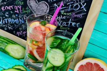 glass water with cucumber and grapefruit on table