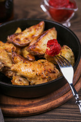 Fried chicken legs with fried potatoes in pan