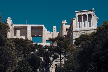 Old building with columns with modern city, urban background. Ancient Greek temple surrounded by park or forest. Cultural and architectural heritage concept.