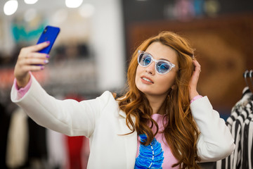 Businesswoman in glasses makes selfie on phone. Concept, shopping.