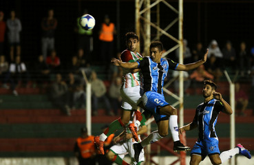 Agropecuario's Barinaga and Almagro's Coronel jump for a header during their Argentine Second Division match in Carlos Casares