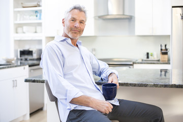 Portrait of gray-haired man holding mug and leaning on kitchen counter, Massachusetts, USA