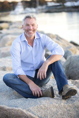 Portrait of gray-haired man sitting on coastal rocks and smiling, Dennis, Massachusetts, USA