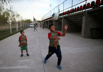 Young supporters of Agropecuario soccer team play outside the Ofelia Rosenzuaig stadium before a match in Carlos Casares