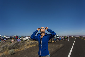 Woman watching solar eclipse, August 8, 2017, Maupin, Oregon, USA