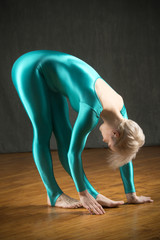 Young blond woman in blue unitard as body sculpture.