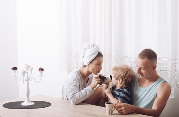 Mother and father and child sit at table in morning. Happy family spend time together,white interior and window on background. Morning routine concept. Family with smiling drinking tea, coffee.