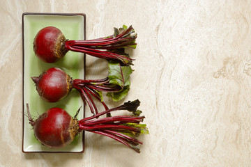 Fresh beetroots on green ceraminc tray on marble with copy space to right