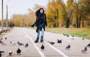 A pretty girl in a coat and jeans with a long scarf happily skates in the autumn park with pigeons. Fighting the autumn depression.